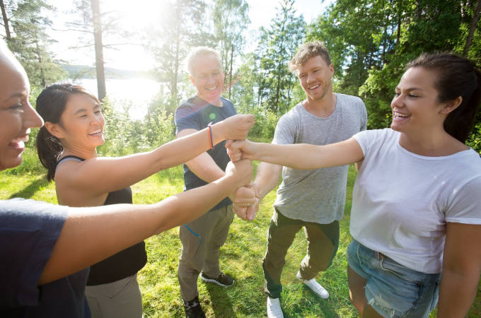 Coworkers Stacking Fists While Standing In Forest